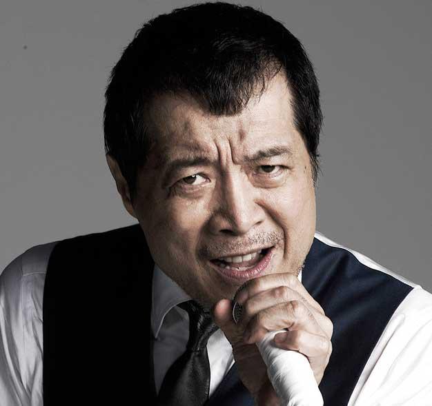 黒と白のシャツを着てマイクを握っている矢沢永吉の画像